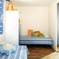 une chambre avec deux lits dans le mobil home 4 places - Camping Les Parcs