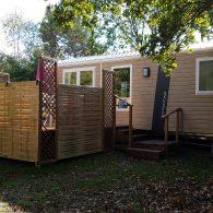 vue sur un mobil home  lodge confort avec sa charmante terrasse aménagée - Camping Les Parcs